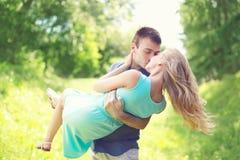Le jeune couple heureux embrasse, homme et femme dans l'amour, prises sur des mains à l'herbe Images libres de droits