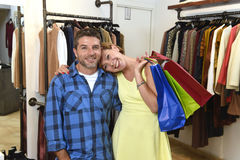 Le jeune couple heureux faisant des emplettes ensemble vêtx au sourire de boutique de mode satisfait en cadeau d'amour Images stock