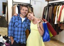 Le jeune couple heureux faisant des emplettes ensemble vêtx au sourire de boutique de mode satisfait en cadeau d'amour Image libre de droits