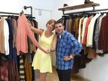 Le jeune couple heureux faisant des emplettes ensemble vêtx au sourire de boutique de mode satisfait en cadeau d'amour Photographie stock libre de droits