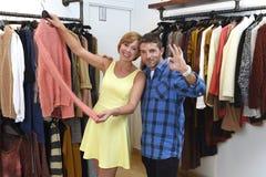 Le jeune couple heureux faisant des emplettes ensemble vêtx au sourire de boutique de mode satisfait en cadeau d'amour Image stock