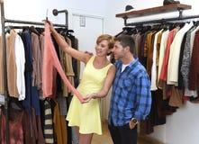 Le jeune couple heureux faisant des emplettes ensemble vêtx au sourire de boutique de mode satisfait en cadeau d'amour Photos stock