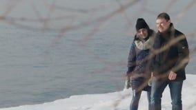 Le jeune couple heureux a l'amusement marchant à côté de la banque de la rivière dehors banque de vidéos