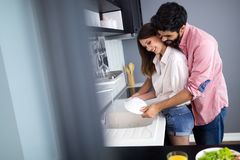 Le jeune couple heureux lave des plats tout en faisant le nettoyage à la maison image libre de droits