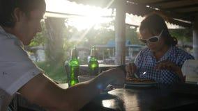 Le jeune couple heureux mangeant le repas boit de la bière en café d'extérieur le jour d'été Image libre de droits