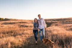 Le jeune couple heureux marche avec le chien photo stock