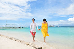 Le jeune couple heureux marche en eau peu profonde sur la plage tropicale Image libre de droits