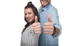 Le jeune couple heureux se tenant ensemble et montrant manie maladroitement vers le haut du signe Image stock