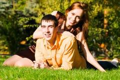 Le jeune couple heureux se trouve sur l'herbe photographie stock libre de droits