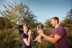 Le jeune couple heureux sur la nature, le garçon donne à fille un chien - terrier de Yorkshire comme cadeau Photos stock