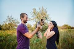 Le jeune couple heureux sur la nature, le garçon donne à fille un chien - terrier de Yorkshire comme cadeau Photographie stock