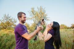 Le jeune couple heureux sur la nature, le garçon donne à fille un chien - terrier de Yorkshire comme cadeau Photos libres de droits