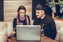 Le jeune couple heureux utilise un ordinateur portable au café Photographie stock