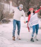Le jeune couple a l'amusement dans le parc et monte sur le magma congelé couvert avec de l'eau fondu Images libres de droits
