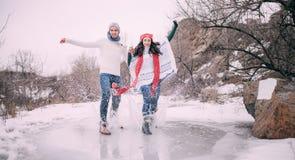 Le jeune couple a l'amusement dans le parc et monte sur le magma congelé couvert avec de l'eau fondu Photos stock