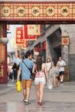 Le jeune couple marche à la région commerciale de Qianmen, Pékin, Chine Photo libre de droits