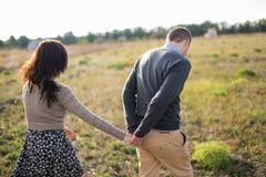 Le jeune couple marche au coucher du soleil tenant des mains Image stock