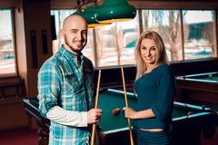 Le jeune couple mignon joue le billard et avoir de l'amusement Photos stock