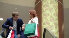 Le jeune couple monte l'escalator avec des paquets des cadeaux pendant des vacances Couples sur l'escalator au centre commercial clips vidéos