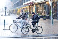 Le jeune couple monte une bicyclette en mauvais temps avec la neige Photos stock