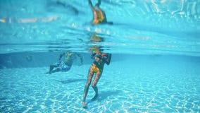Le jeune couple nage dans le jour ensoleillé de piscine extérieure clips vidéos