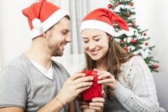 Le jeune couple ouvre le boîte-cadeau de Noël Images libres de droits