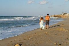 Le jeune couple a plaisir à marcher sur une plage floue à Photographie stock