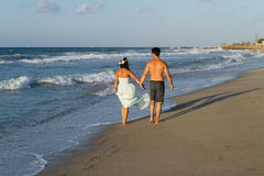 Le jeune couple a plaisir à marcher sur une plage floue à Photo libre de droits