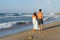 Le jeune couple a plaisir à marcher sur une plage floue à Image libre de droits