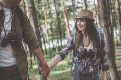 Le jeune couple positif dans l'amour marche dans la forêt Images libres de droits