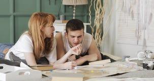Le jeune couple prévoit leur itinéraire de voyage utilisant la carte du monde et d'autres accessoires s'étendant dans le lit à la clips vidéos