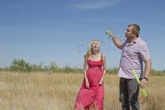 Le jeune couple prend les bulles de savon énormes Photos libres de droits