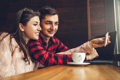 Le jeune couple prend le selfie et apprécie le café dans le café tout en à l'aide d'un ordinateur portable Image stock