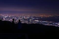 Le jeune couple regardant la ville de nuit s'allume du haut de la montagne Image libre de droits