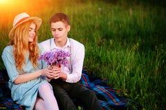 Le jeune couple se reposant sur le plaid en parc et regard au coucher du soleil, homme donne à son amie un bouquet des lilas Image libre de droits