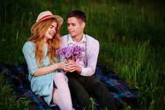 Le jeune couple se reposant sur le plaid en parc et regard au coucher du soleil, homme donne à son amie un bouquet des lilas Photographie stock libre de droits