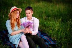 Le jeune couple se reposant sur le plaid en parc et regard au coucher du soleil, homme donne à son amie un bouquet des lilas Images libres de droits