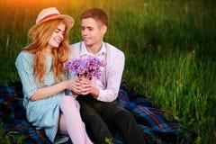 Le jeune couple se reposant sur le plaid en parc et regard au coucher du soleil, homme donne à son amie un bouquet des lilas Photos libres de droits
