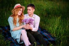 Le jeune couple se reposant sur le plaid en parc et regard au coucher du soleil, homme donne à son amie un bouquet des lilas Image stock