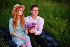 Le jeune couple se reposant sur le plaid en parc et regard au coucher du soleil, homme donne à son amie un bouquet des lilas Photos stock