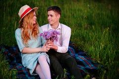 Le jeune couple se reposant sur le plaid en parc et regard au coucher du soleil, homme donne à son amie un bouquet des lilas Photographie stock
