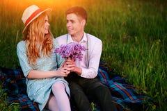 Le jeune couple se reposant sur le plaid en parc et regard au coucher du soleil, homme donne à son amie un bouquet des lilas Images stock