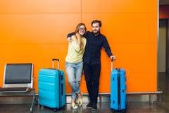 Le jeune couple se tient dans l'aéroport sur le fond orange entre deux valises bleues Type avec la barbe dans la chemise noire et photographie stock
