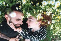 Le jeune couple se trouve sur le champ avec des marguerites photos stock