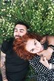 Le jeune couple se trouve sur le champ avec des marguerites photos libres de droits