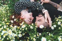 Le jeune couple se trouve sur le champ avec des marguerites photo stock