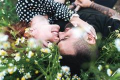 Le jeune couple se trouve sur le champ avec des marguerites image stock