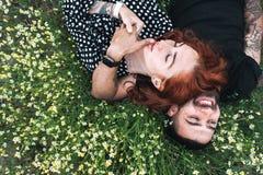 Le jeune couple se trouve sur le champ avec des marguerites images stock