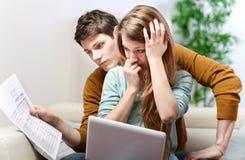 Le jeune couple soucieux consulte leur compte bancaire Photographie stock libre de droits