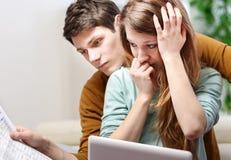 Le jeune couple soucieux consulte leur compte bancaire Photo libre de droits